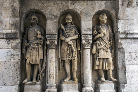 matthias church: Stone carved warriors stand against a wall at the Matthias Church in Budapest in Hungary. The Matthias Church sits on a hill overlooking the Danube River.