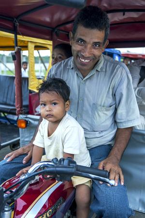 rio amazonas: Un conductor de tuk tuk y su hijo esperan a los clientes en Indiana, una ciudad en el r�o Amazonas en Per�. El r�o Amazonas se elev� a niveles r�cord en 2012, inundando muchas ciudades a lo largo de sus orillas.