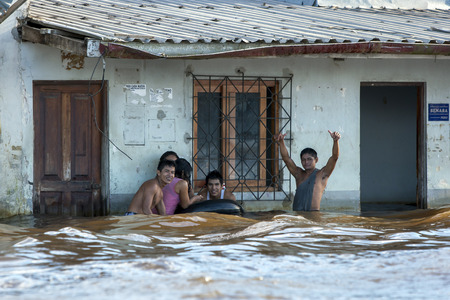 rio amazonas: A group of locals play in a flooded street in Iquitos in Peru. The Amazon River had risen to one of its highest levels on record flooding many communities lining its banks.