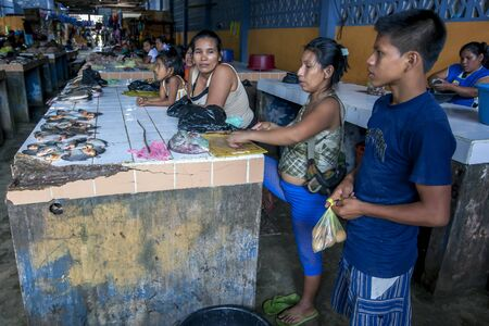 rio amazonas: A family display their catch of piranha at the fish market in Indiana, a town on the Amazon River in Peru. The Amazon River rose to record levels in 2012, flooding many towns along its banks. Editorial
