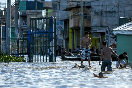 rio amazonas: A group of locals play in a flooded street of Iquitos in Peru. The Amazon River had risen to one of its highest levels on record flooding many communities lining its banks.