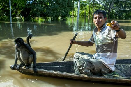 rio amazonas: A man and monkey paddle in a canoe over the flooded Monkey Island near Iquitos in Peru. The Amazon River had risen to one of its highest levels on record flooding many communities lining its banks. Editorial