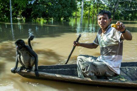 río amazonas: Un hombre de la paleta y el mono en una canoa sobre la Isla de los Monos inundado cerca de Iquitos en Per�. El r�o Amazonas se hab�a elevado a uno de sus niveles m�s altos registrados inundando muchas comunidades que bordean sus orillas.