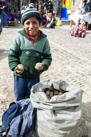 sacred valley of the incas: A young boy selling potatoes in the market at Pisca in the Sacred Valley of the Incas in Peru. Editorial