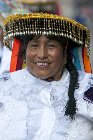 plaza de armas: A colourfully dressed lady poses for a phototgraph in Plaza de Armas in Cusco during the May Day parade in  Peru.