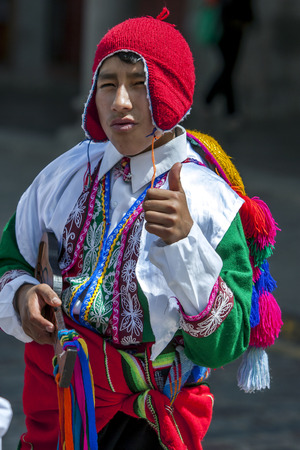 plaza de armas: A colourfully dressed boy performs down Plaza de Armas in Cusco during the May Day parade in  Peru.