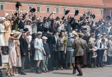 cinta pelicula: extras de cine para realizar una escena de película en la Plaza del Castillo en la ciudad vieja de Varsovia en Polonia.