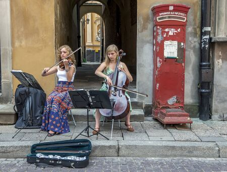 cellos: A pair of young musicians playing a violin and a cello perform in the Old Town of Warsaw in Poland. Editorial