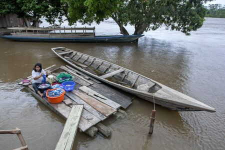 peru amazon: A Peruvian lady washing clothes in a flooded section of the Amazon River town of Indiana in Peru.