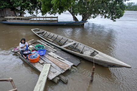 río amazonas: Una se�ora peruana lava la ropa con una secci�n inundada de la ciudad de R�o Amazonas Indiana en Per�.