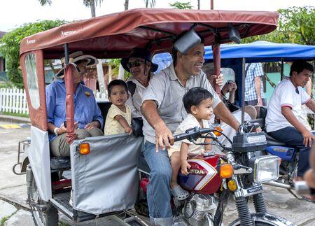 rio amazonas: Un hombre y sus hijos llevan a los turistas para un paseo en Tuk Tuk Tuk a trav�s de Indiana, una ciudad en el r�o Amazonas en Per�. El r�o Amazonas se elev� a niveles r�cord en 2011, inundando muchas ciudades a lo largo de sus orillas.