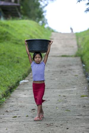 rio amazonas: A Peruvian girl carrying washing down to the bank of the Amazon River in Indiana, Peru.