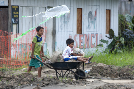 indiana: Children flying a kite whilst riding in a wheel barrow in the Amazon River town of Indiana, Peru. Editorial