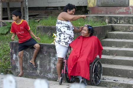 río amazonas: Una se�ora tiene el pelo hecho en la calle en la ciudad de R�o Amazonas Indiana, Per�.