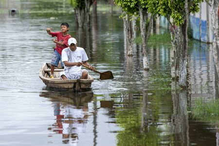flooded: A man and boy paddle their boat through the flooded section of Indiana, a town on the Amazon river in Peru. The Amazon River rose to record levels in 2011, flooding many towns along its banks.