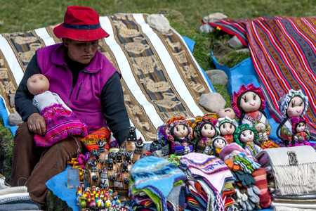 souvenirs: A lady dressed in traditional Peruvian costume selling dolls and souvenirs near Cusco in Peru.