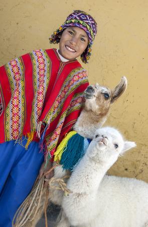cusco: A boy dressed in traditional Peruvian costume with his llamas in Cusco, Peru. Editorial