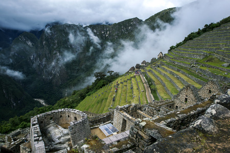 metres: The incredible ancient ruins of Machu Picchu in Peru. Machu Picchu is a 15th-century Inca site located 2,430 metres (7,970 ft) above sea level and is situated on a mountain ridge above the Sacred Valley which is 80 kilometres northwest of Cusco and throug