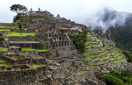 metres: The incredible ancient ruins of Machu Picchu in Peru showing the stone terraces . Machu Picchu is a 15th-century Inca site located 2,430 metres (7,970 ft) above sea level and is situated on a mountain ridge above the Sacred Valley which is 80 kilometres n