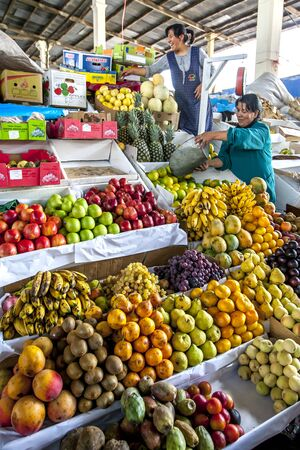cusco: Ladies stack fruit at their colourful stall in a market in Cusco in Peru. Editorial