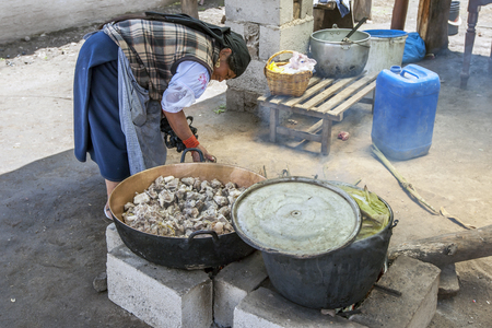 coals: A lady keeps an eye on the coals cooking a pot of meat and vegetables at Peguche in Ecuador.