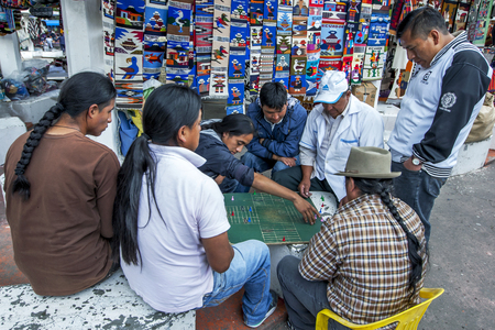 playing the market: Indian men playing a board game in the Indian Market at Otavalo, Ecuador.