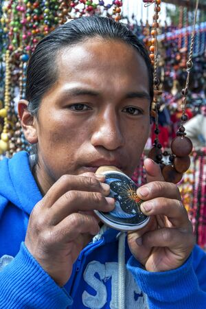 playing the market: An Indian man playing a colourful flute at the Indian Market in Otavolo in Ecuador.