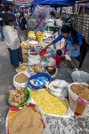 A lady serves a customer at her produce stall in the Indian Market in Otavolo in Ecuador.