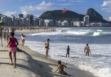 lowers: A helicopter lowers a rescued swimmer onto Copacabana Beach in Rio de Janeiro, Brazil.