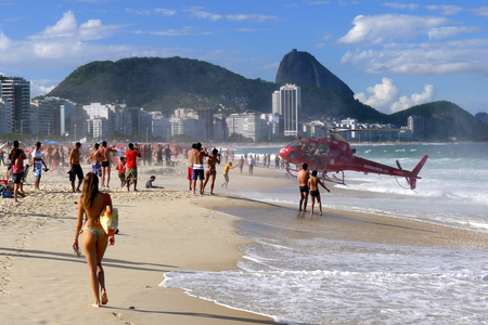 A helicopter lands on Copacabana Beach at Rio de Janeiro, Brazil after rescuing a person from the surf. Stock Photo - 56235334
