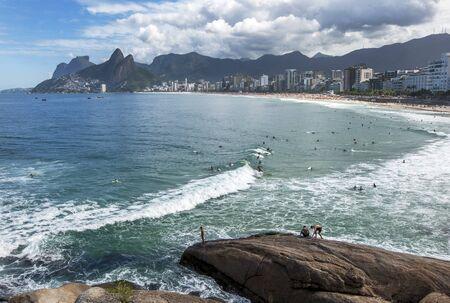 surfers: Surfers ride a wave at Ipanema Beach in Rio de Janeiro in Brazil.
