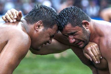 wrestlers: Exhausted wrestlers face each other at the Kemer Turkish Oil Wrestling Festival, Kemer, Turkey. Editorial