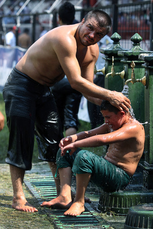 cool down: A father helps his son cool down after he was defeated on the final day of competition at the Kirkpinar Turkish Oil Wrestling Festival in Edirne in Turkey.
