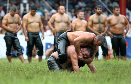 edirne: A middle weight wrestler places his opponent in a head lock during a fierce battle at the Kirkpinar Turkish Oil Wrestling Festival in Edirne in Turkey. Editorial