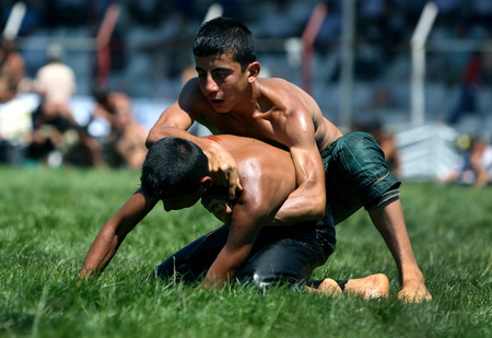 opponent: A young wrestler attempts to overpower his opponent at the Elmali Turkish Oil Wrestling Festival in Turkey. Editorial