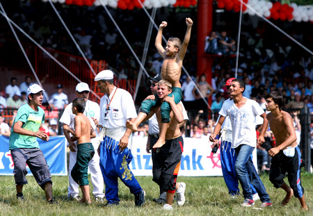 edirne: A young wrestler celebrates after winning his division at the Kirkpinar Turkish Oil Wrestling Festival, Edirne, Turkey, 2009. Editorial