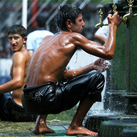 bout: A young wrestler cools off at the water fountain after his bout at the Kirkpinar Turkish Oil Wrestling Festival, Edirne, Turkey.