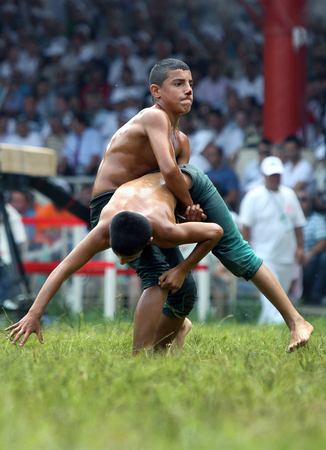 bloodied: A bloodied wrestler lifts his opponent from the ground during the final day of competition at the Kirkpinar Turkish Oil Wrestling Festival in Edirne in Turkey. Editorial