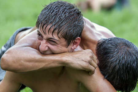opponents: A wrestler sinks his teeth into his opponents arm during a fiery contest at the Kirkpinar Turkish Oil Wrestling Festival in Edirne in Turkey.