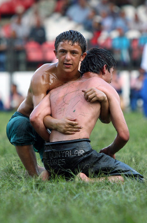 edirne: A defeated wrestler is comforted by a friend after being defeated at the Kirkpinar Turkish Oil Wrestling Festival in Edirne in Turkey. Editorial