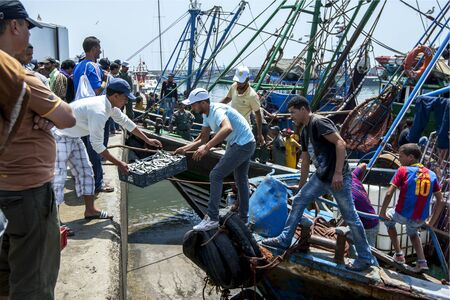 18th: Fishermen unload their catch from a trawler at the busy harbour at Essaouira in Morocco. The present city of Essaouira was built during the 18th century by Mohammed III who wished to reorient his kingdom toward the Atlantic for security reasons. French en