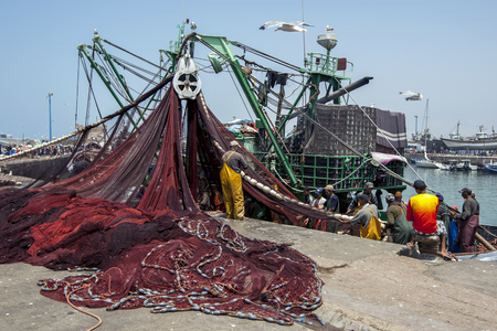 18th: Fishermen gather fish from their nets in the busy harbour at Essaouira in Morocco. Their nets are unloaded from the trawler with the aid of a crane. The present city of Essaouira was built during the 18th century by Mohammed III who wished to reorient his Editorial