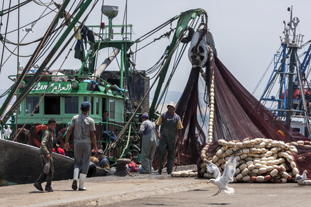 18th: Fishermen return with their catch to the busy harbour at Essaouira in Morocco. Their nets are unloaded with the aid of a crane. The present city of Essaouira was built during the 18th century by Mohammed III who wished to reorient his kingdom toward the A Editorial