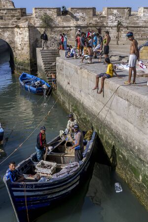 18th: Fishermen return with their catch to the busy fishing harbour at Essaouira in Morocco. The present city of Essaouira was built during the 18th century by Mohammed III who wished to reorient his kingdom toward the Atlantic for security reasons. French engi