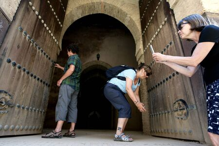 A group of tourists photographing the doors to the old grainaries of the Heri es-Souni in Meknes, Morocco.