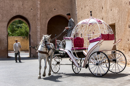 A horse and carriage doing a u-turn outside the old grainaries of the Heri es-Souni in Meknes, Morocco.