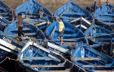 18th: Boys stand amongst the many fishing boats in the port of Essouaira, Morocco. The present city of Essaouira was built during the 18th century by Mohammed III who wished to reorient his kingdom toward the Atlantic for security reasons. French engineer, Theo Editorial