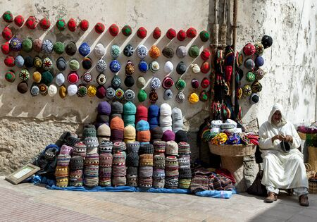 beanies: A man selling beanies in Essaouira, Morocco. The present city of Essaouira was built during the 18th century by Mohammed III who wished to reorient his kingdom toward the Atlantic for security reasons. French engineer, Theodore Cornut built the city with  Editorial