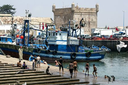 18th: The fishing harbour at Essaouira with the fort tower in the background, Morocco. The present city of Essaouira was built during the 18th century by Mohammed III who wished to reorient his kingdom toward the Atlantic for security reasons. French engineer,  Editorial