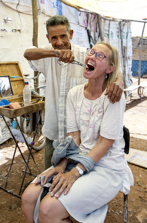 tooth extraction: The local dentist displays his tooth extraction technique at the Tahanoute market, Morocco.